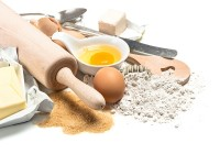 Baking ingredients flour, eggs, yeast, sugar, butter. Wooden kitchen utensils rolling pin and spatula. Food background